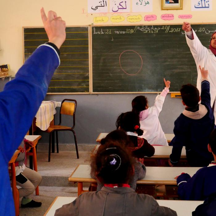 Classroom with children at desks facing their teacher. Two children have their hands raised.
