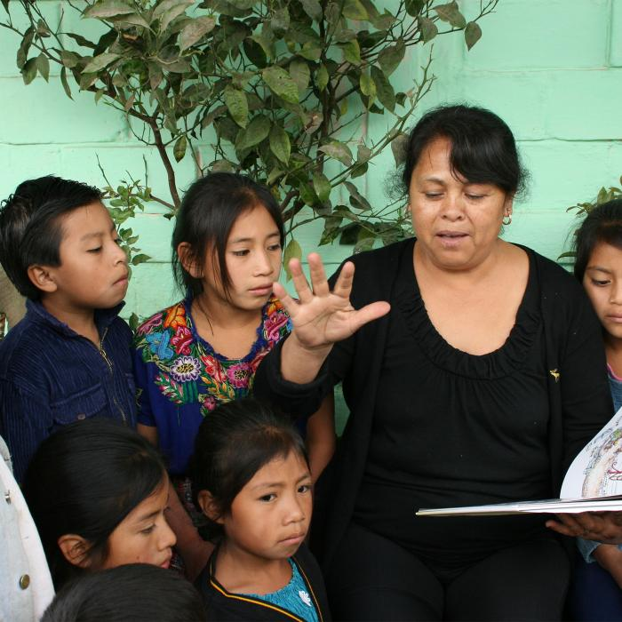 A teacher reads to her students in Guatemala