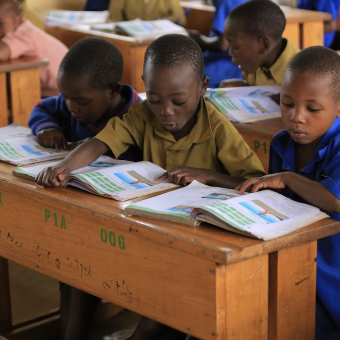 Photo: Primary 1 students practice reading with their Kinyarwanda textbooks during a Kinyarwanda Reading Camp 2019, Burera District.