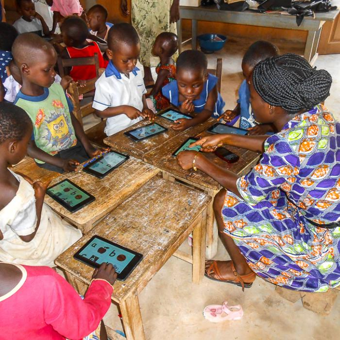 A teacher uses tablet computers to teach young children.