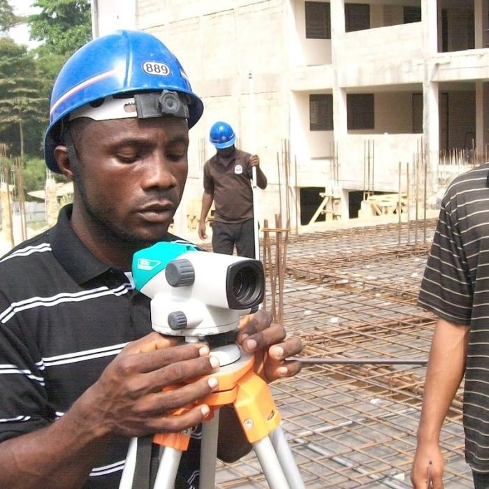 Men performing survey practicals on campus