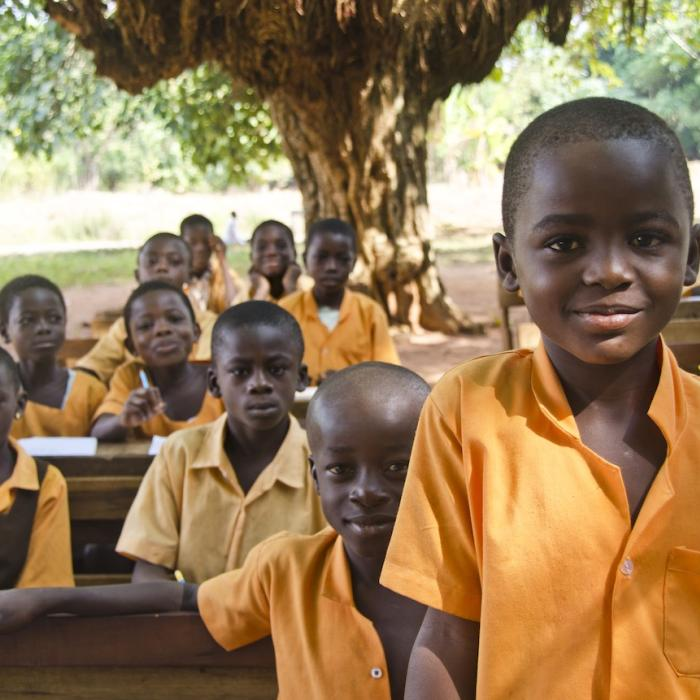 Students at a Ghana school under the trees.