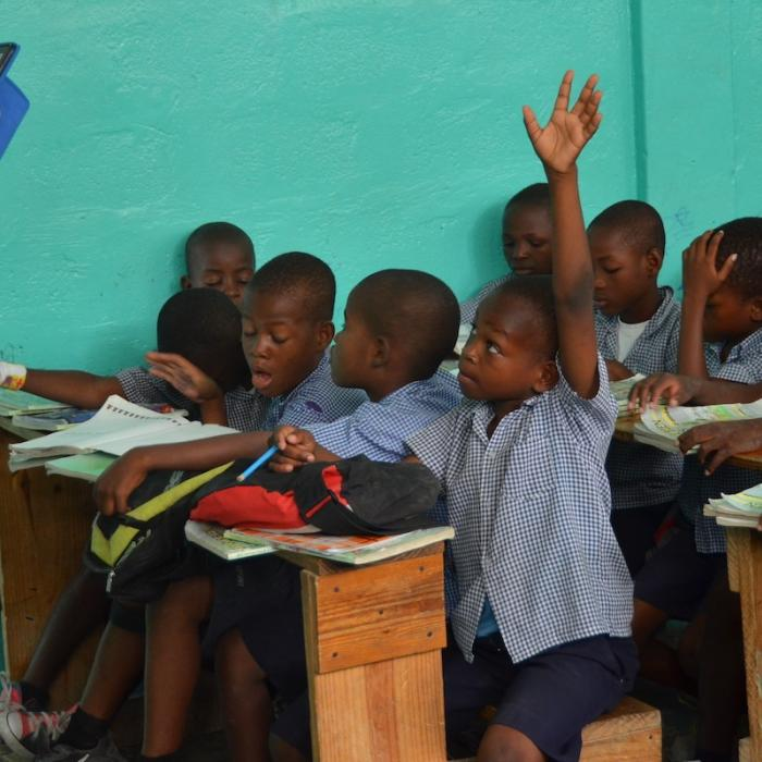A young Haitian boy raises his hand in class.