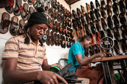 Two men sitting and working in front of two walls covered in shoes