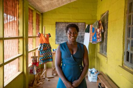 Annet, the Executive Director of Safeplan Uganda stands in a room smiling at the camera with two dresses behind her